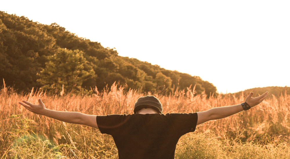 Man in field outstretched arms